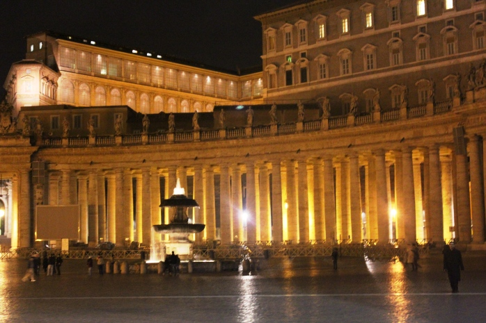 Night view of St. Peter's Square: one of the fountains and the columns surrounding the square
