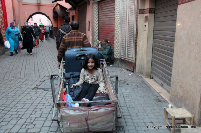My daughter is being hauled in a luggage cart toward our riad, in Medina, Marrakech
