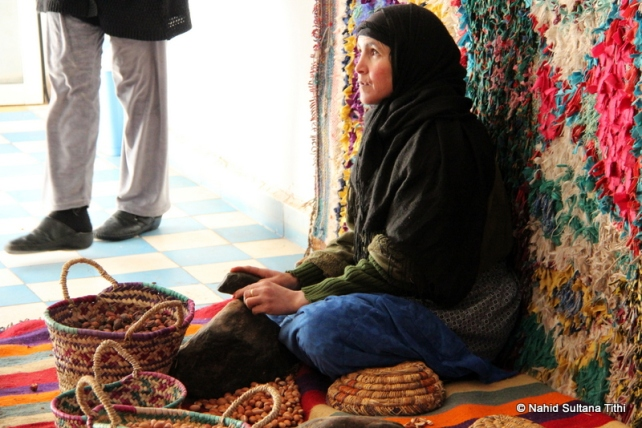 A lady breaking argan nuts in a road-side cosmetics store, on our way to Ouarzazate