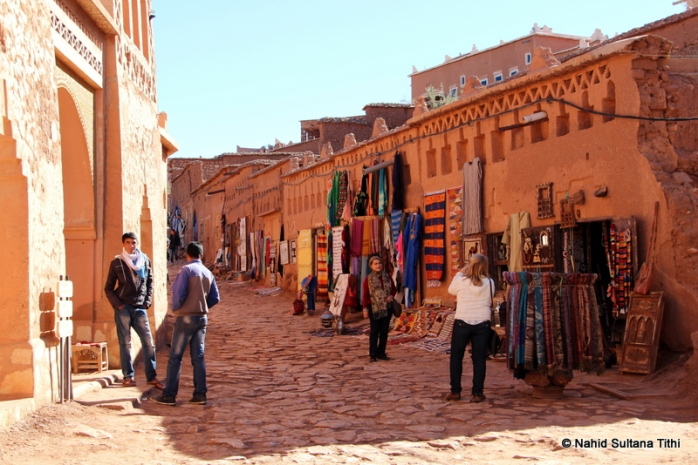 Walking back to our taxi from Ait Ben Haddou, going thru some Berbere shops. You can see their hand-made rugs hanging in one of the stores