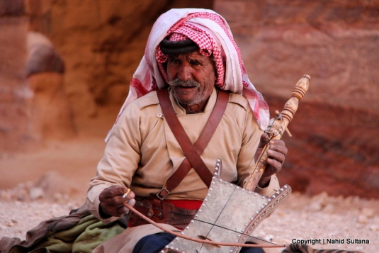 Man playing a very old instrument, called Rebabh, near Khazana in Petra, Jordan