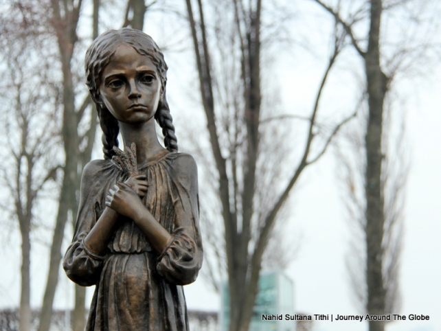 A starving little girl in front of Famine Monument in Kiev, Ukraine