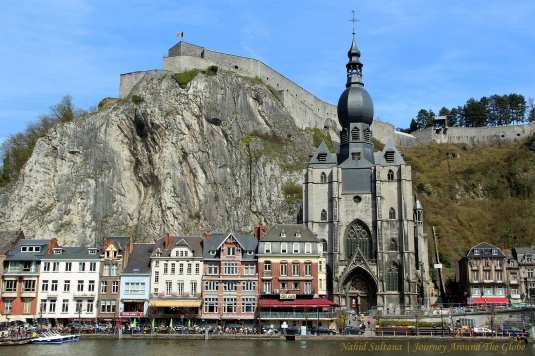 Collegiate Cathedral of Dinant and the citadel in the backdrop with River Meuse flowing in the front in Dinant, Belgium
