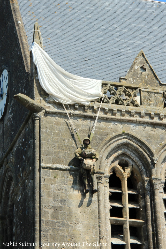 A dummy dangling from St. Mere Eglise commemorating paratrooper John Steele whose parachute got caught in this church's spire on June 6, 1944, Normandy, France