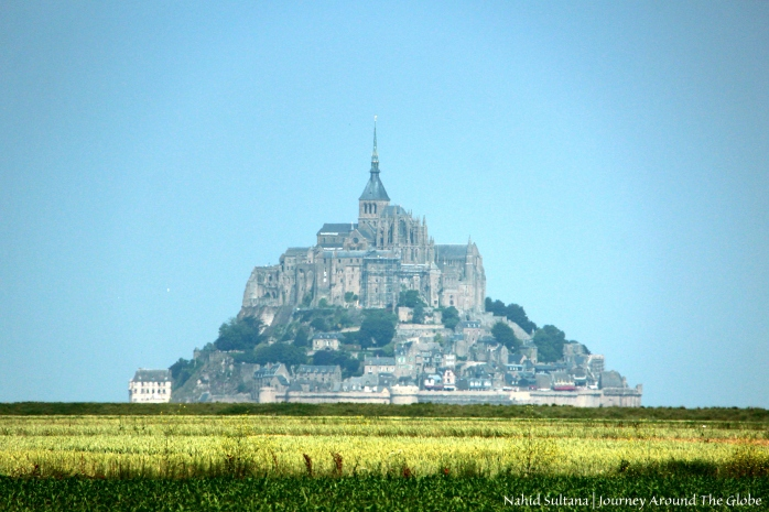 Pyramidal shape of Mont St. Michel from afar in Normandy, France