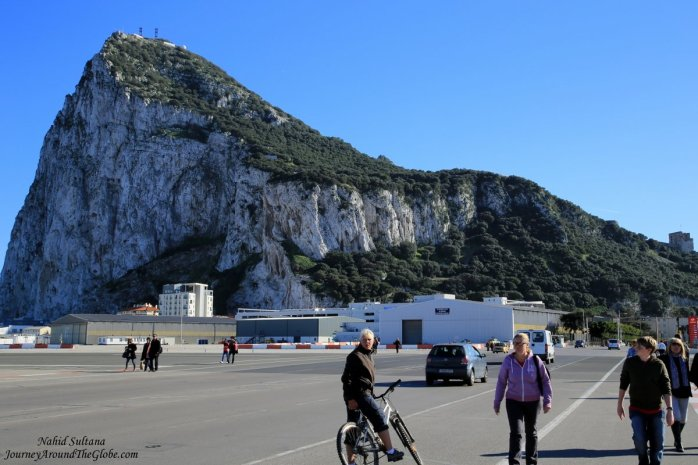 People crossing runway of Gibraltar Airport in front of The Rock (big hill in the back) in Gibraltar
