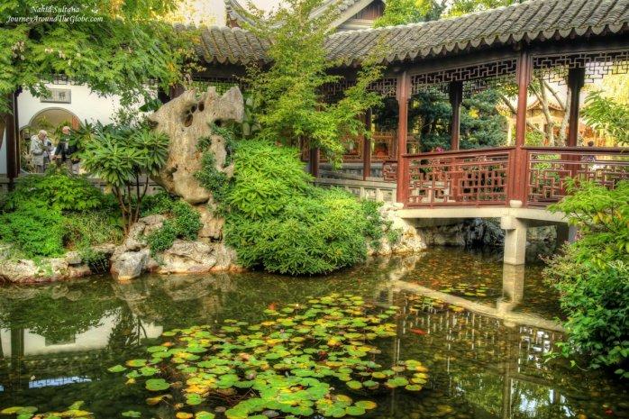 Trees, pond, and bridge in Lan Su Chinese Garden in Portland, Oregon