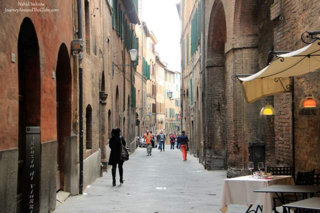 Walking thru an ancient alley in Old Siena, Italy