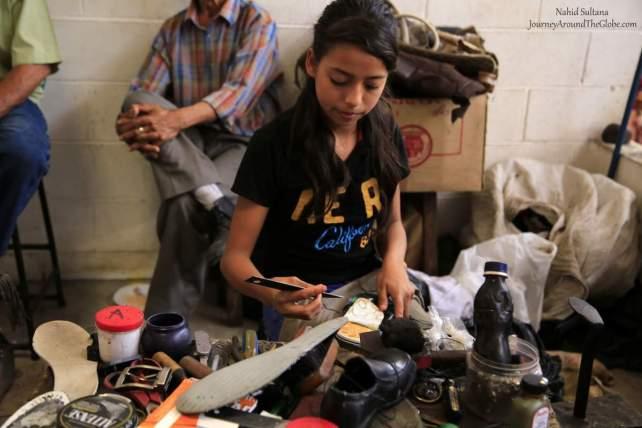 A little girl fixing shoes inside Marcado Municipal de Suchitoto, El Salvador